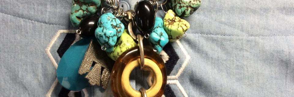 This handmade necklace is made with turquoise, green stones and a leather pendant. The len