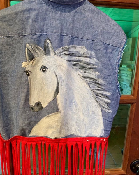 20223 Jamee Handpainted Chambray Vest had a white horse on the back and added red cotton fringe. Sizes come small - large.]